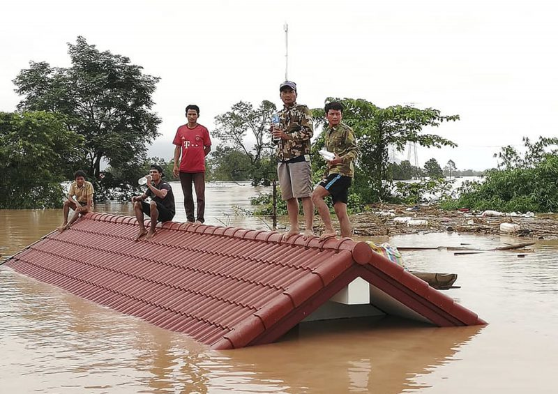 Villagers take refuge on a rooftop above flood waters from a collapsed dam in the Attapeu district of southeastern Laos. (Attapeu Today via AP, File)
